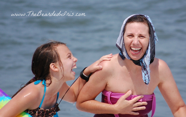 laughing mother and daughter at the beach